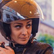 Kobieta zapina kask motocyklowy z interkomem